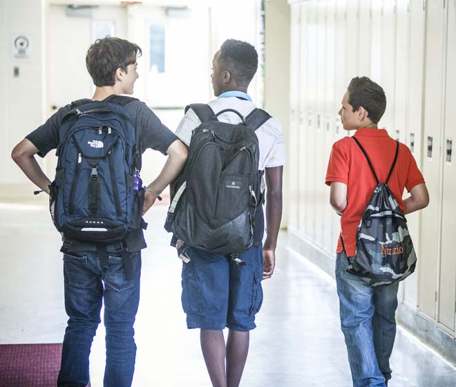 3 Middle School boys walking in a school hallway with backpacks