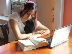Photo of high-school student with laptop, headset and a book sitting at the table, studying
