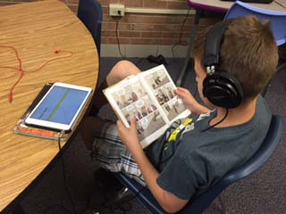 Boy sitting at a table. He has headphones on and is reading a graphic novel.