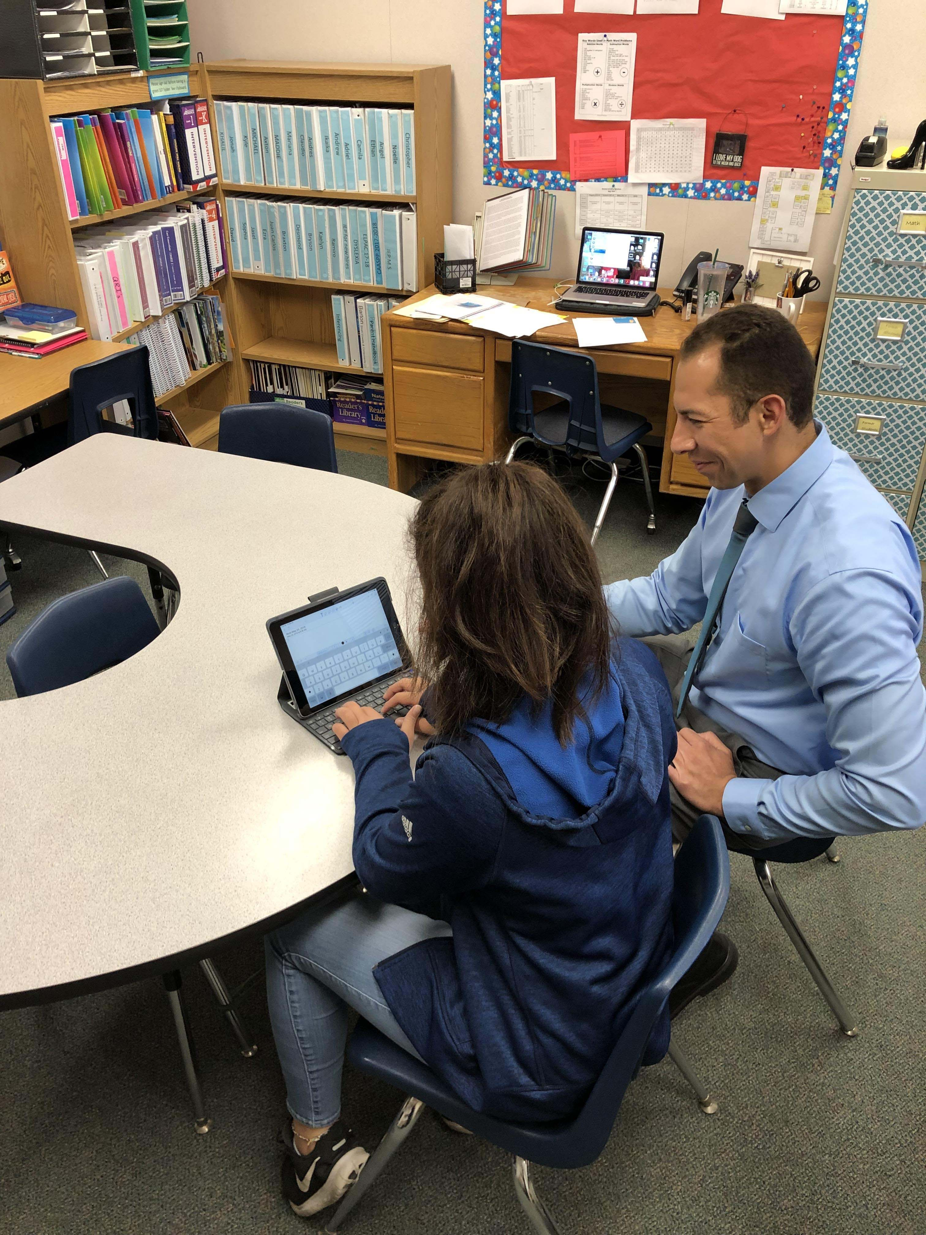 Jerry working with a student in the classroom on a device.