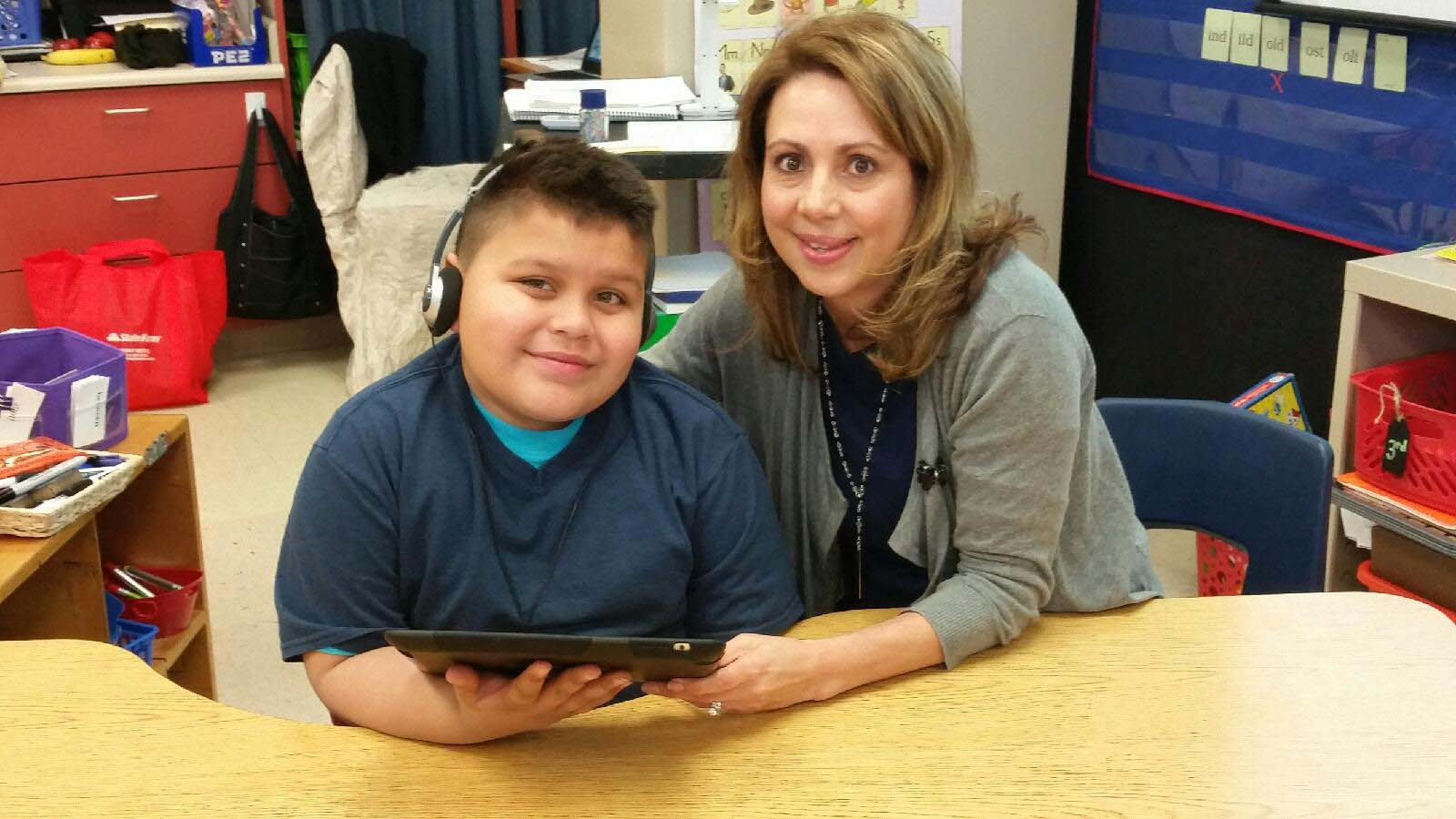 Mrs. Reyes sitting with a student in class. He has headphones on and is reading a tablet.