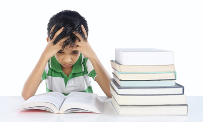 Young boy at desk with a printed books, hands on head, troubled look