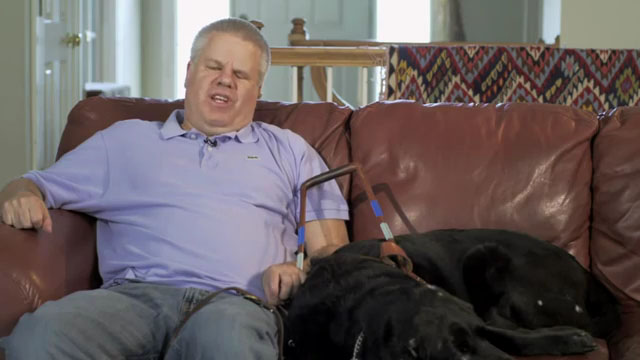 Blind author Peter Altschul and guide dog sitting on sofa