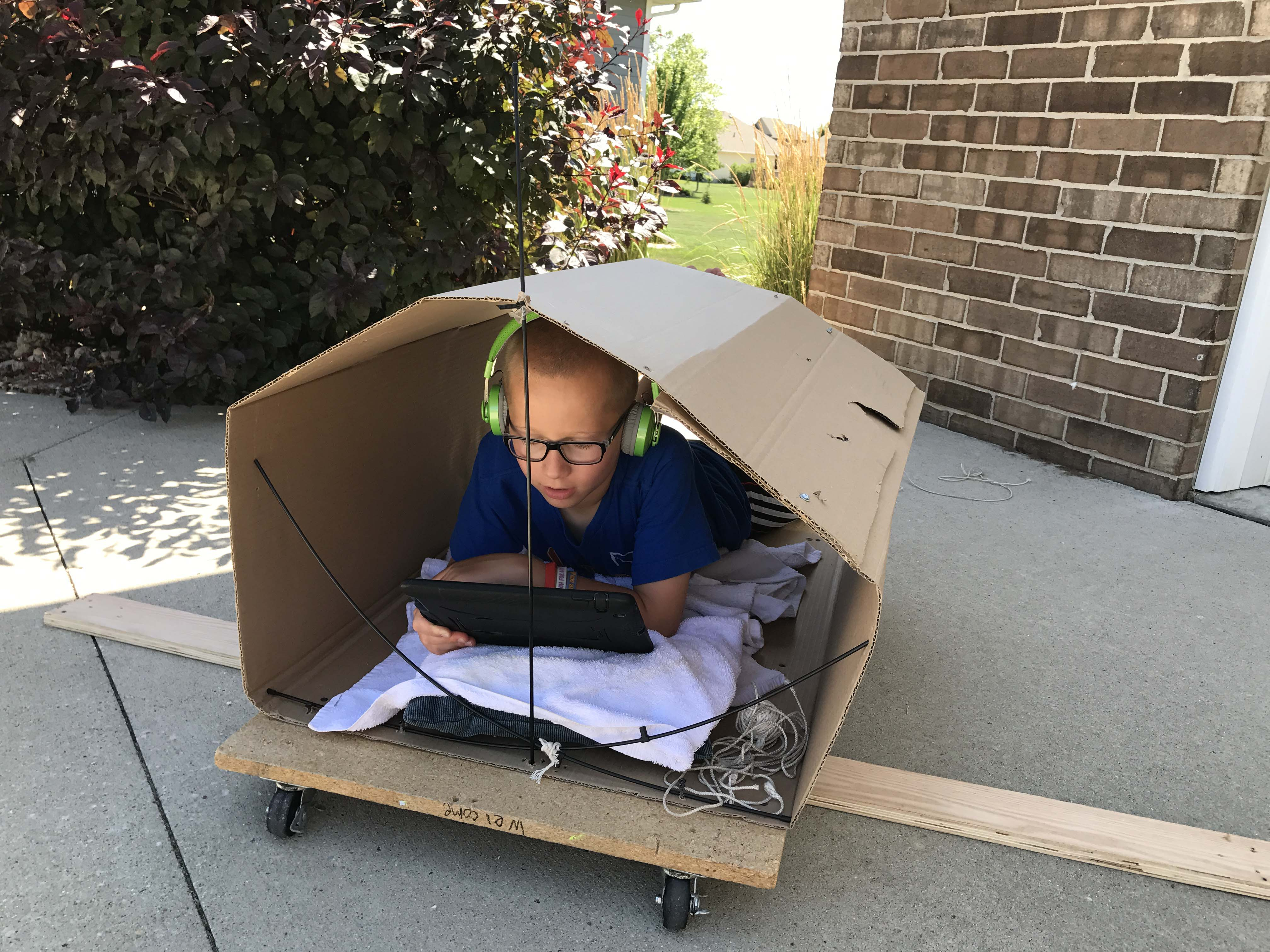Dyslexic student ear reading in a fort he built outside on a summer's day.