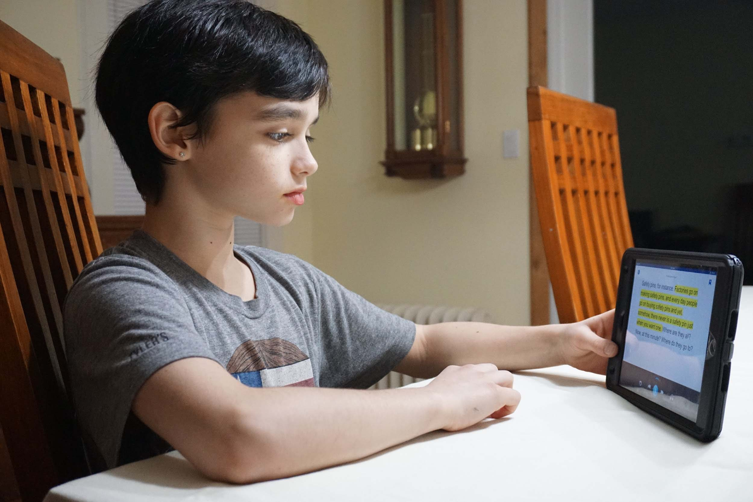 Boy Reads Using Device