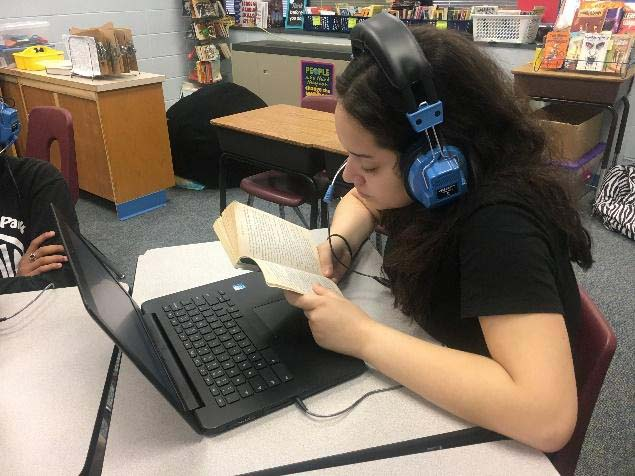 Girl Reads Using Assistive Technology