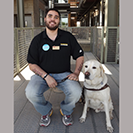 Bryan Duarte sitting on bench with service dog beside him