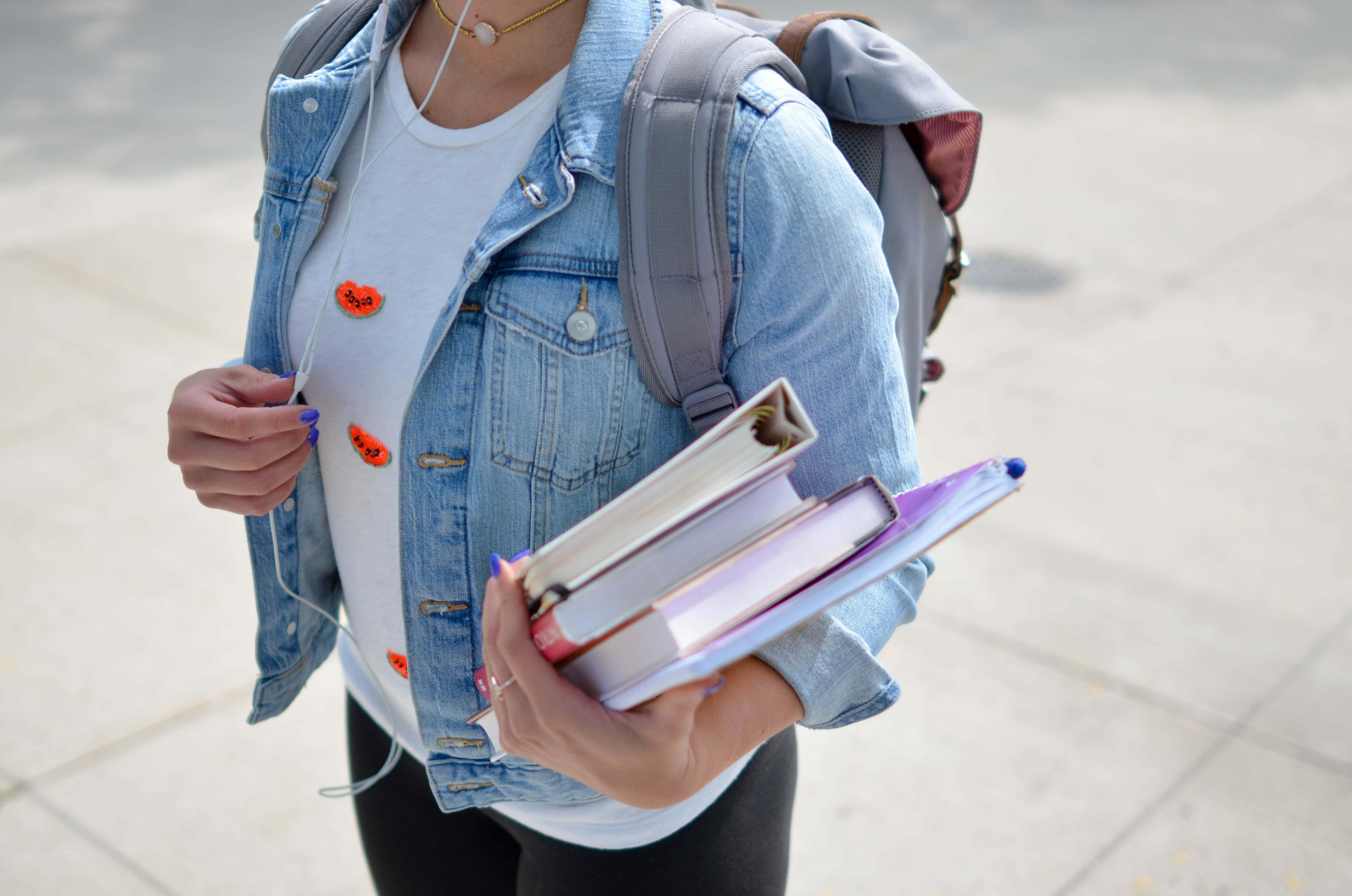 Torso of girl student holding books and a backpack