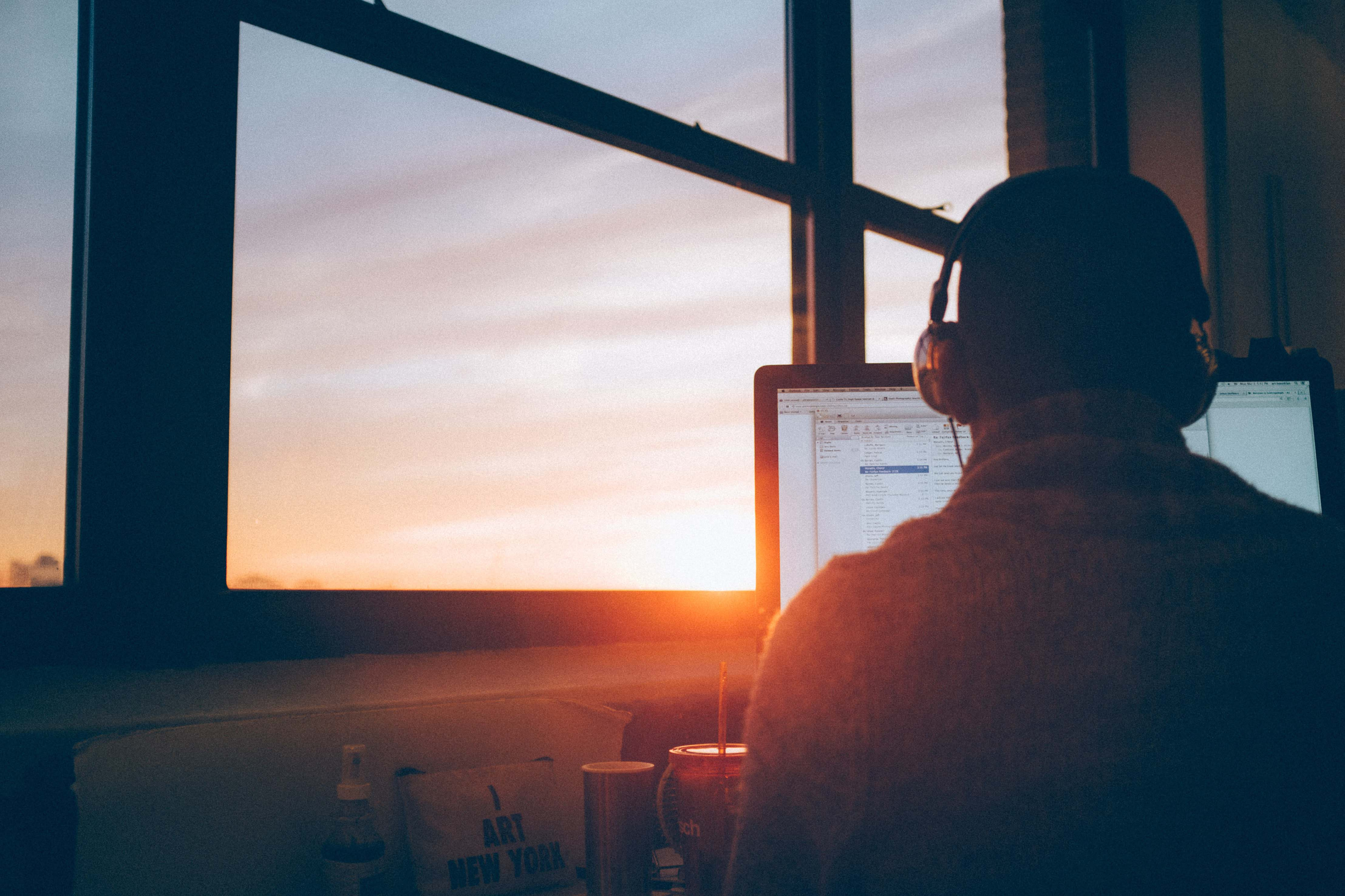 Man wearing headphones sitting in front of a computer with his back to the camera. He is sitting at a window and the sun is setting.
