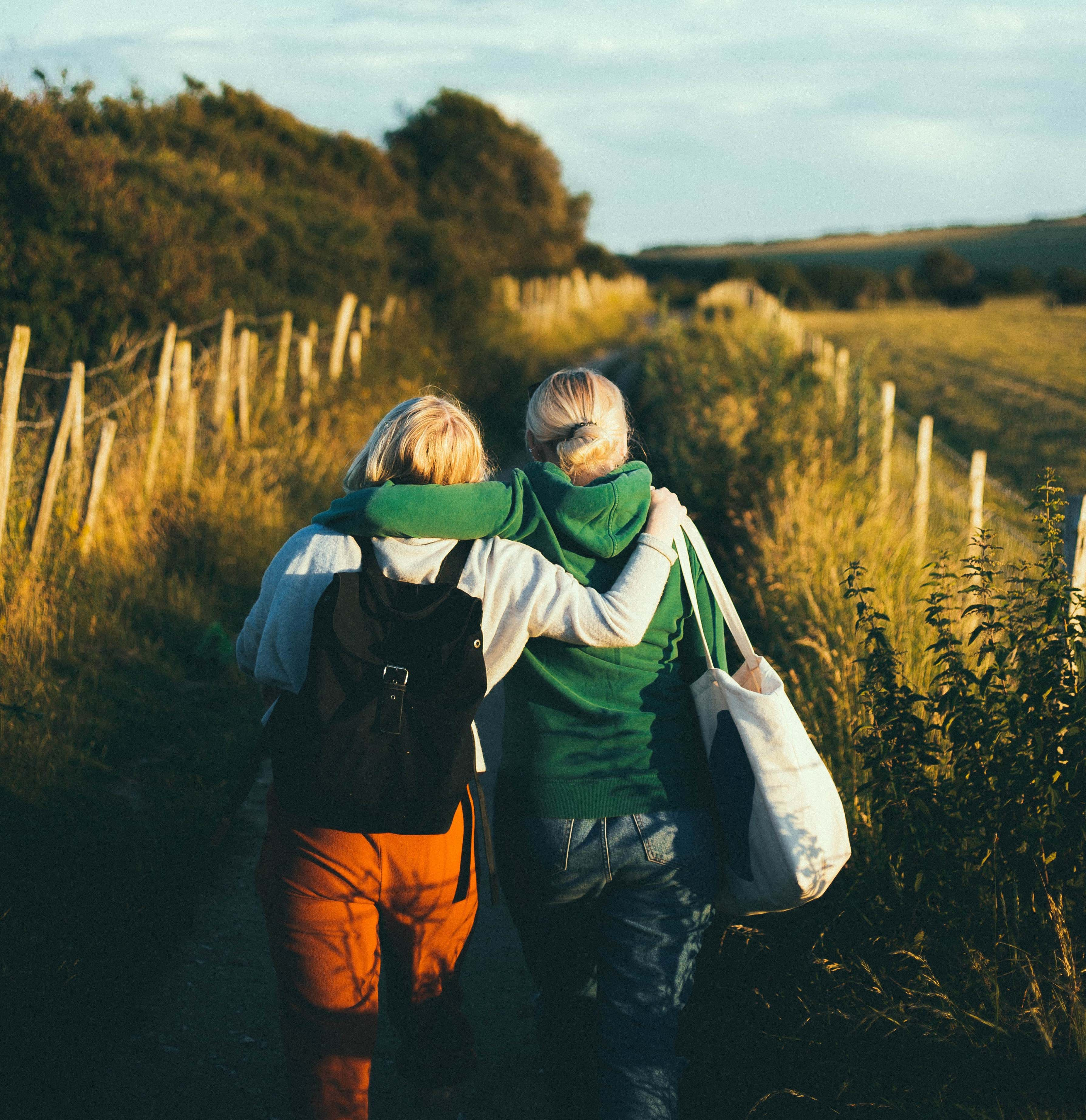 Two women with blonde hair walking down a path with their arms around each others shoulders. Their backs are to the camera. There is tall green grass on either side of a the path and an open, blue sky above them.