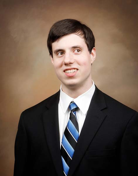 Portrait of Timothy Jones. Timothy can be seen from mid torso up and is sitting in front of a brown background. He is wearing a black suit, white collared shirt, and a blue and black diagonally striped tie.
