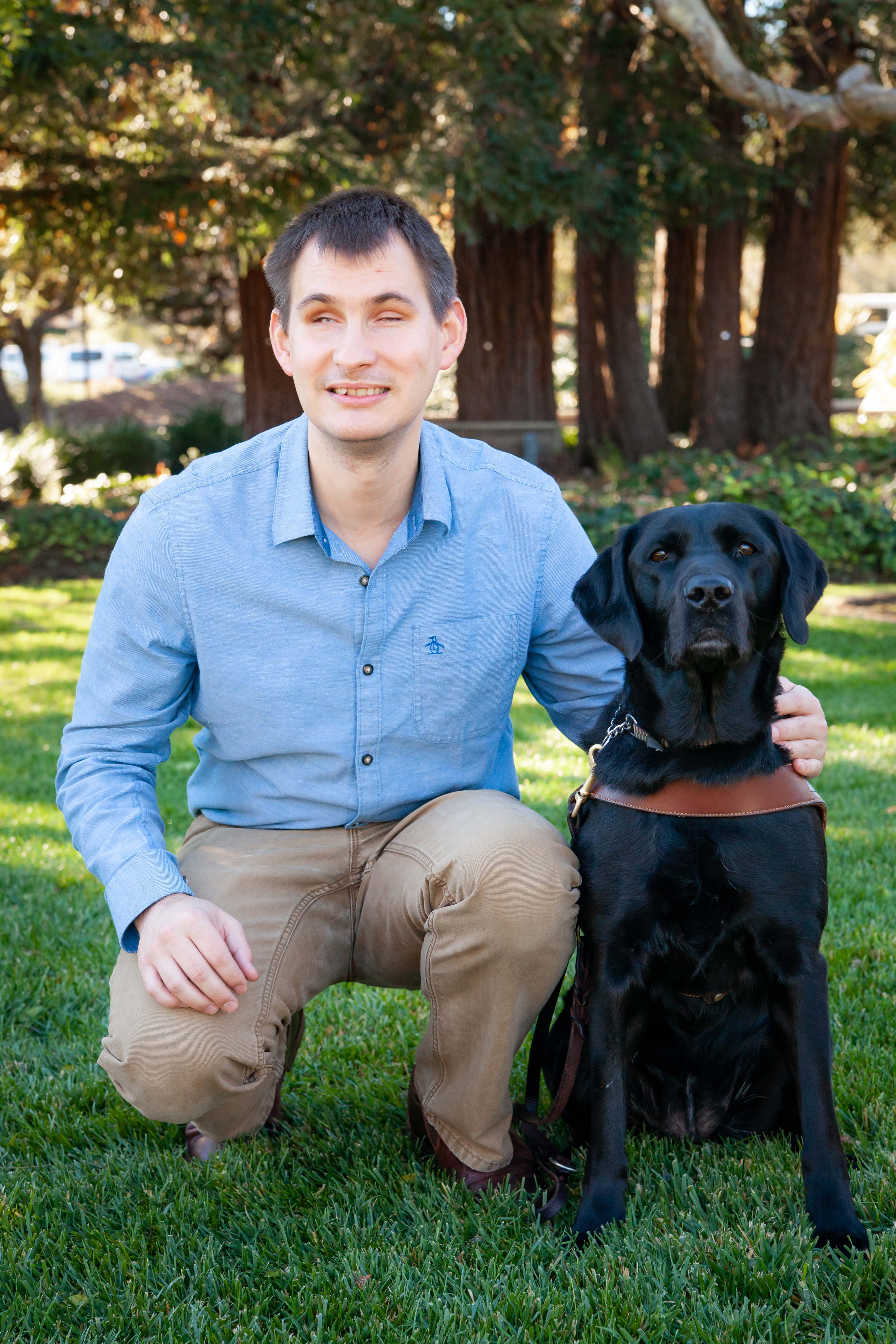 Jake Koch from Guide Dogs for the Blind and his guide dog, Forli. Jake and Forli are standing in a grassy area with trees in the background. Jake is wearing a blue button down shirt and brown pants and is squatting next to Forli, who is a black labrador retriever.