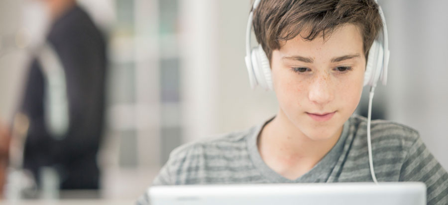 student on a computer listening to an audiobook with headphones