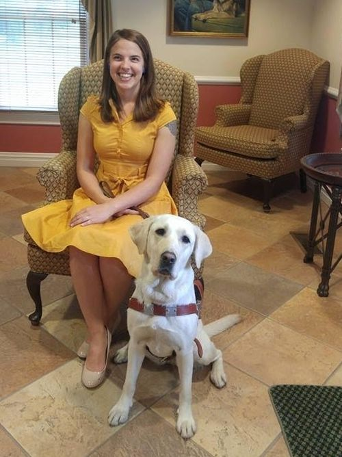 College Success mentor Abigail Lanier sitting with her seeing-eye dog