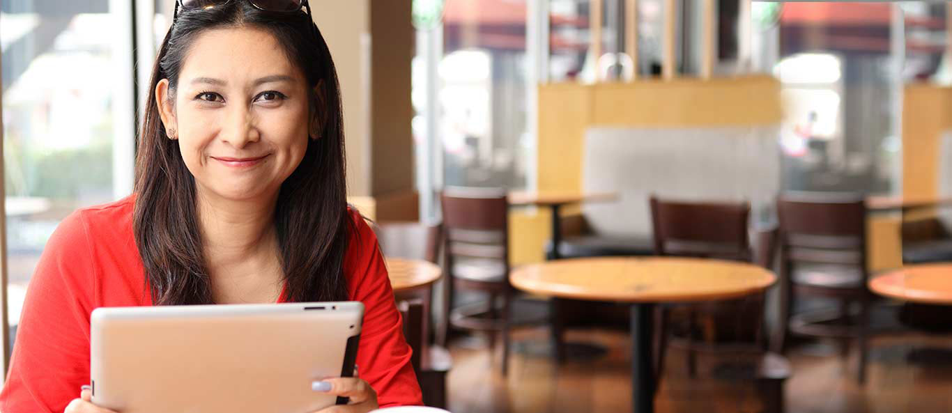 woman sitting with a tablet in a cafe looking straight, smiling