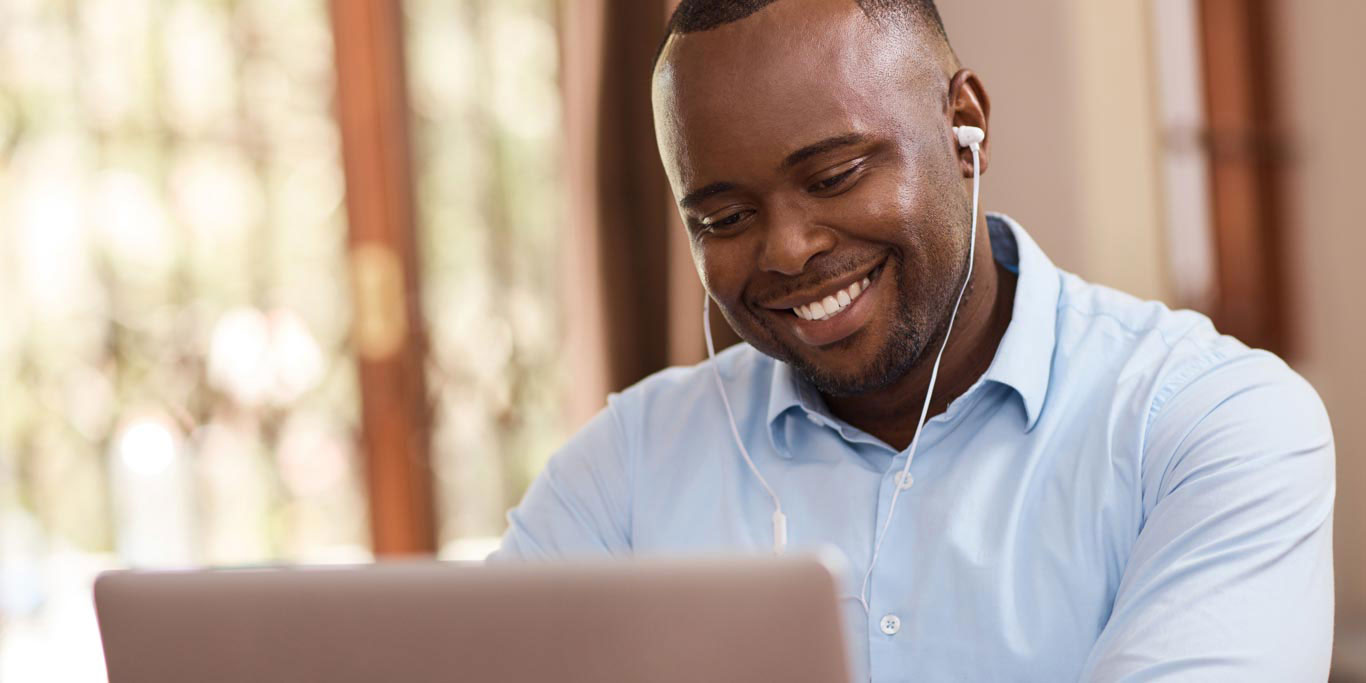 man listening to an audiobook and smiling