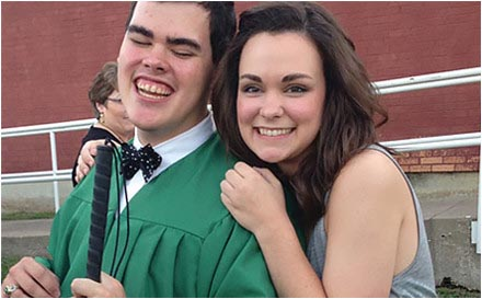 Student who is blind in graduation cap and gown with sister