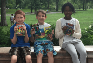 Kids reading Goosebumps books in the park