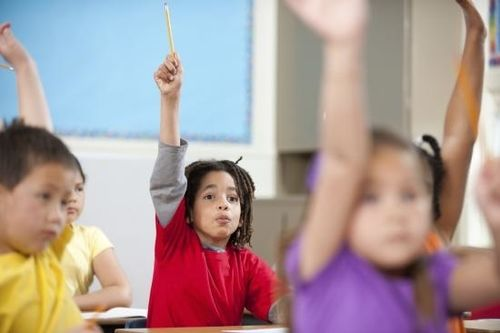 Kids with hands raised in classroom